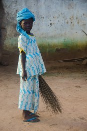 Yassin sweeps her compound.