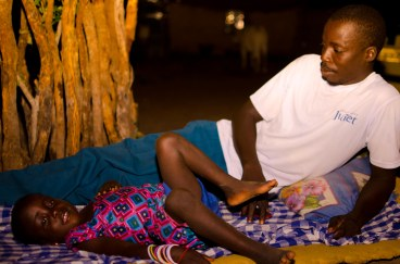 Allagie and his daughter Ida relax outside on a hot night.
